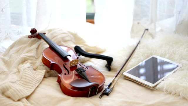 vídeos y material grabado en eventos de stock de cozy image of a violin and a digital device on blankets and a window behind - color crema