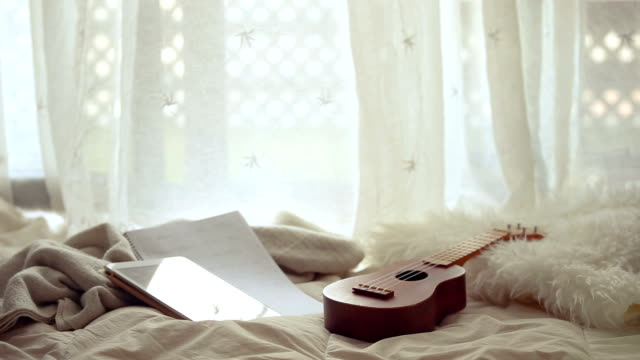 vídeos y material grabado en eventos de stock de cozy image of an ukulele, digital device and music sheets on blankets in front of a window - color crema