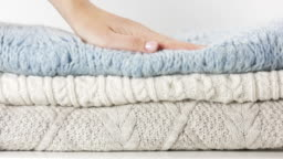 Cozy sweaters are lying in a pile