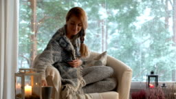 Cozy winter lifestyle. Young happy woman drinking cup of coffee wearing knitted sweater sitting home by the big window with winter snow background