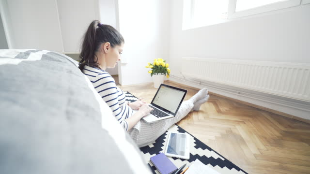 Cozy young woman at home using a laptop.