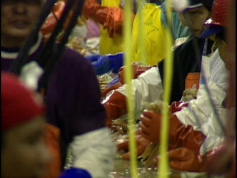 zo, ms, crab pieces moving slowly down conveyor belt in crab processing plant, workers working on either side of belt, dutch harbor, unalaska, alaska, usa  - ヘルメット点の映像素材/bロール