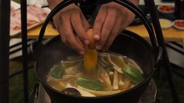 stockvideo's en b-roll-footage met breek een ei in shabu pot tijdens het kamperen in de buitenlucht - japanse gerechten