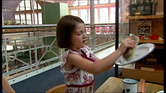stockvideo's en b-roll-footage met background report east london bethnal green museum of childhood int young girl playing at washing tin plate at table mother and children at mock up... - kinderporno