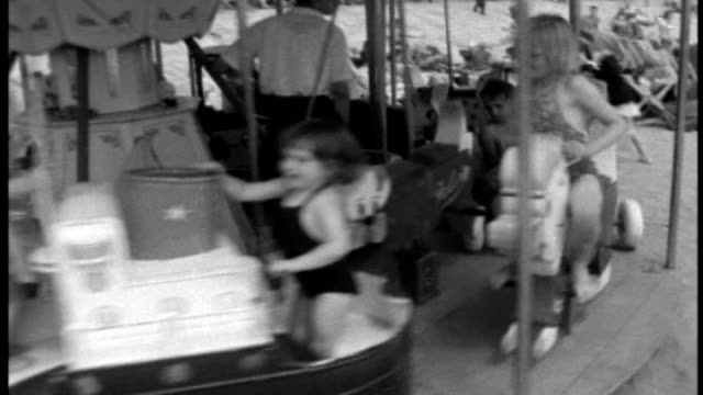 background report lib england kent ramsgate ext b/w archive footage of children on merrygoround at seaside / children on swing boats / holidaymakers... - ramsgate stock videos & royalty-free footage