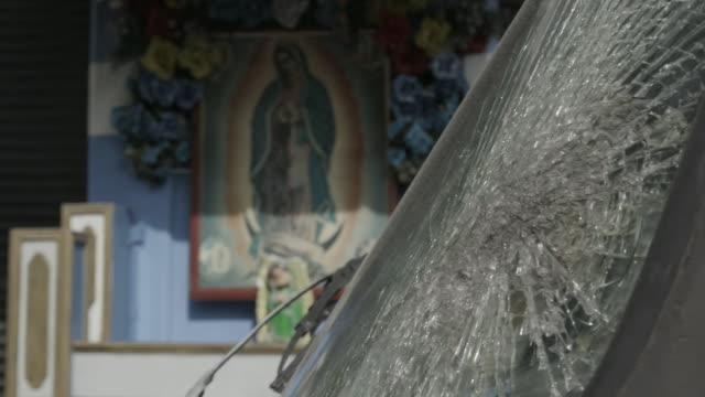 Cracked windshield and picture of virgin mary, rack focus