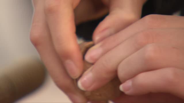 stockvideo's en b-roll-footage met cracking a walnut open with both hands - notendop