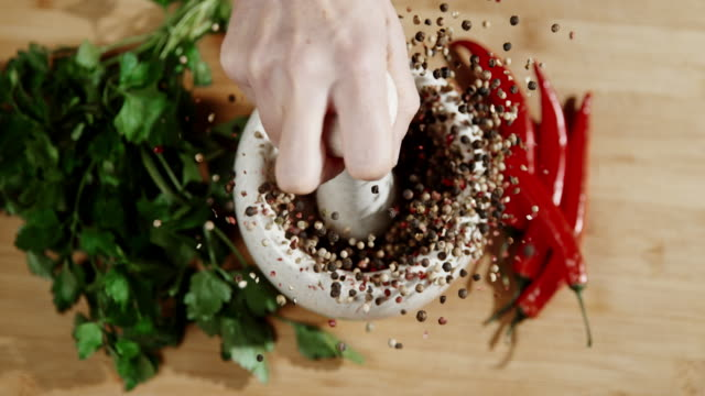 slo mo cracking peppercorns in the mortar - macinare video stock e b–roll