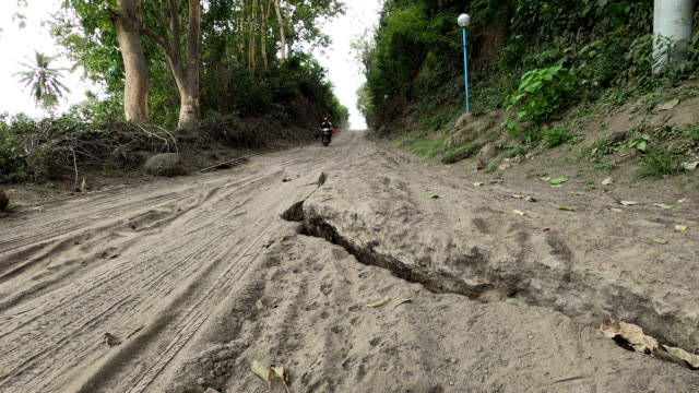 cracks damage road due to uplift from magma rising beneath taal volcano in philippines - dirt track stock videos & royalty-free footage