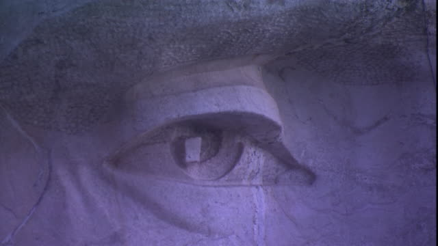 Cracks in the rock on Mount Rushmore run across the face of a carved image of a U.S. President.