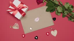 Craft letter with a kiss sticker on a pink background. A bouquet of red roses