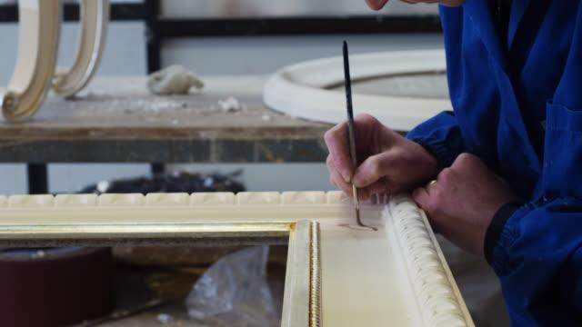 vídeos y material grabado en eventos de stock de carpintero artesano pintando un cuadro con cepillo - marco