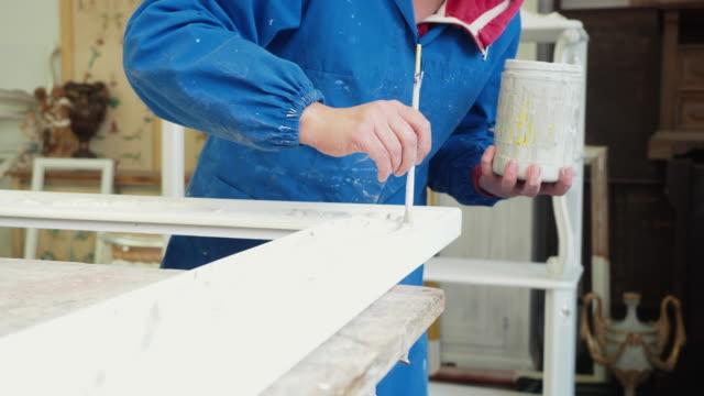 Handwerker-Schreiner einen Rahmen mit Pinsel malen