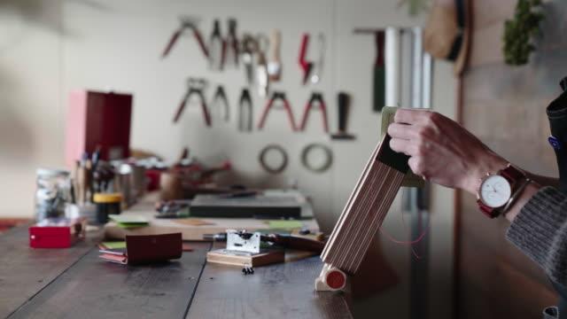 handwerker-hand nähen ein portemonnaie aus leder - kunsthandwerkliches erzeugnis stock-videos und b-roll-filmmaterial