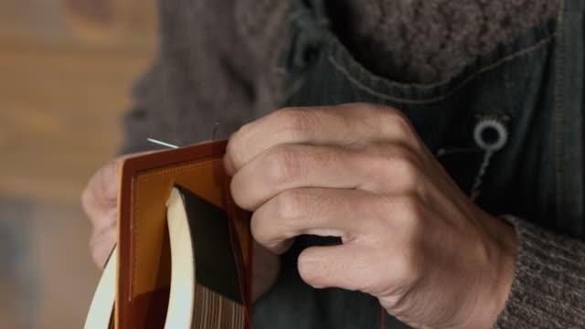 vídeos de stock e filmes b-roll de craftsman hand sewing a leather wallet - couro