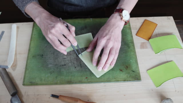 craftsman handcrafting leather wallet - home made stock videos and b-roll footage