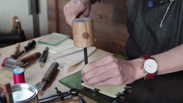 handwerker machen löcher in leder bereit zum nähen - kunsthandwerkliches erzeugnis stock-videos und b-roll-filmmaterial