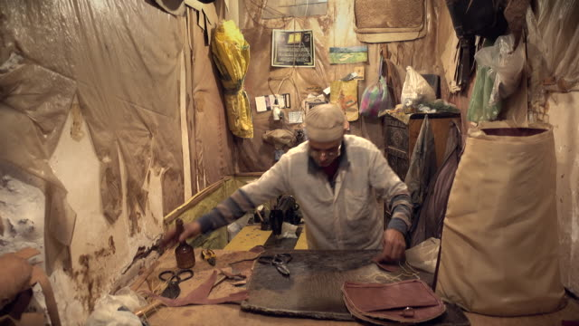Craftsman making leather bag