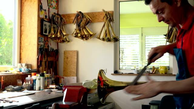 craftsman polishing trumpet - trumpet stock videos and b-roll footage