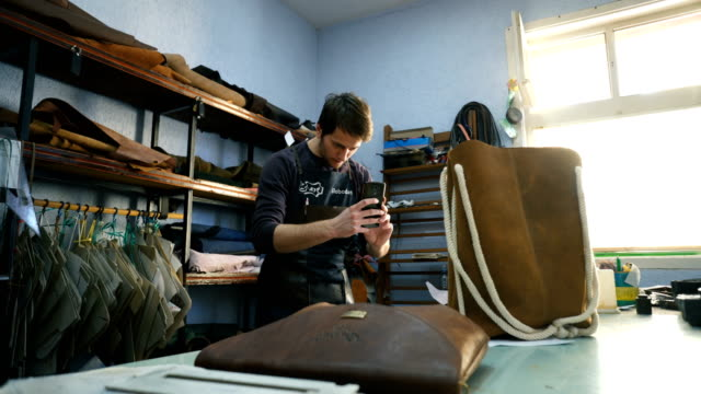 craftsman preparing photos for online shop - leather stock videos and b-roll footage