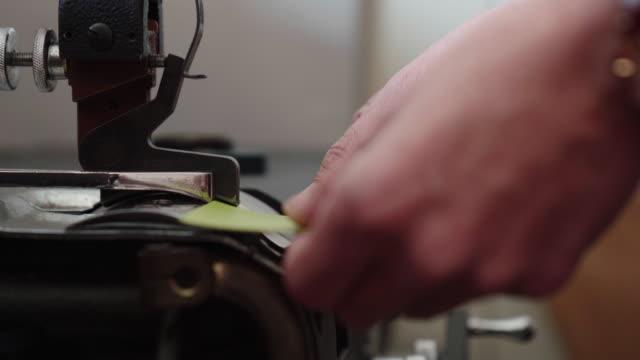 handwerker, die leder bereit zum nähen von hand drücken - kunsthandwerkliches erzeugnis stock-videos und b-roll-filmmaterial