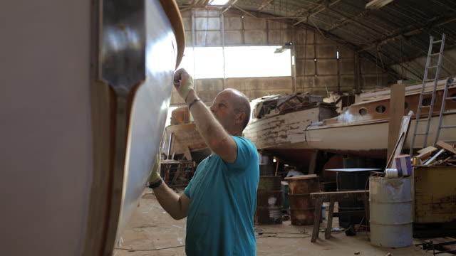 craftsman sanding wooden boat in boat yard workshop - sanding stock videos & royalty-free footage