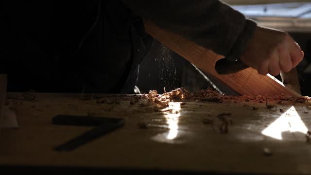 CU LA craftsman using traditional hand tool in woodwork workshop