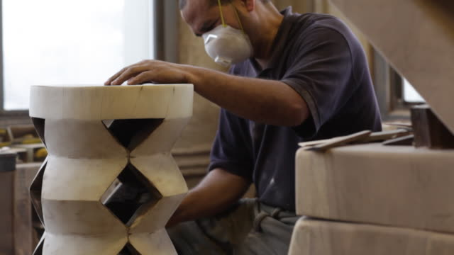 A craftsman wears a mask as he uses a power sander on wooden furniture.