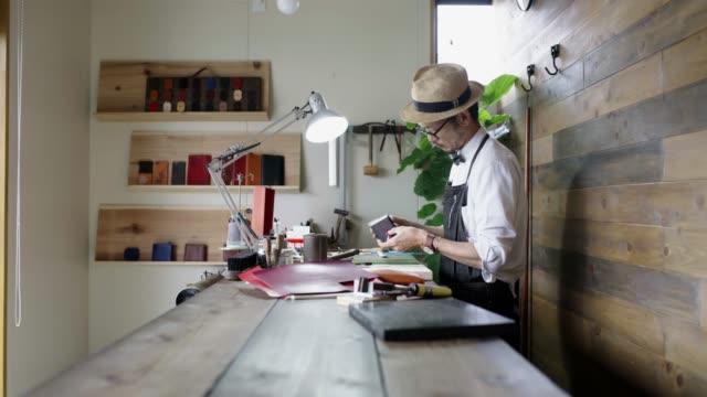 handwerker arbeiten an einem leder-produkt - leder stock-videos und b-roll-filmmaterial