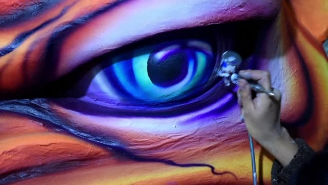 Craftsmen and women add the final touches to their enormous floats the day before Colombia's largest celebration the Blacks and Whites carnival part...