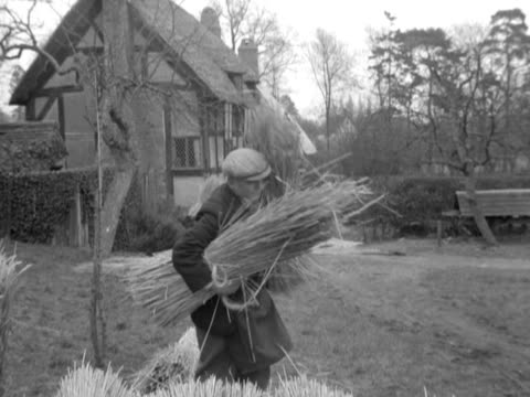 craftsmen prepare to rethatch the roof of anne hathaway's cottage - strohdach stock-videos und b-roll-filmmaterial