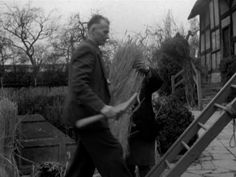 craftsmen start to rethatch the roof of anne hathaway's cottage - tetto di paglia video stock e b–roll