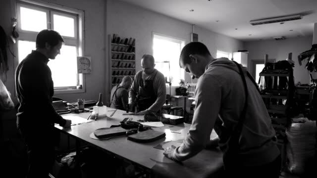 vídeos de stock e filmes b-roll de craftsmen work in workshop - couro