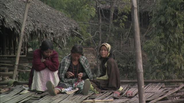 vídeos de stock, filmes e b-roll de craftspeople bead jewelry by hand near a grass hut in india. - conta artigo de armarinho