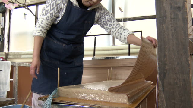 a craftswoman picks up a sheet of miyama washi paper from a mesh bamboo screen, japan - washi paper stock videos & royalty-free footage