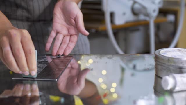 stockvideo's en b-roll-footage met craftswoman werken met donkere inkt op matrijs oppervlak voor diepdruk afdrukken - litho