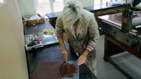 stockvideo's en b-roll-footage met craftswoman die van toepassing zijn donkere inkt bezig mal oppervlak voor diepdruk afdrukken - litho