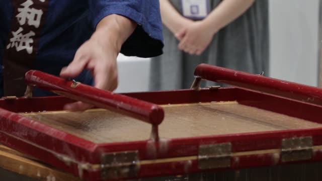 a craftworker makes washistyle paper during a demonstration at the monozukuri takumi no waza expo in tokyo japan on thursday aug 11 a visitor right... - washi paper stock videos & royalty-free footage