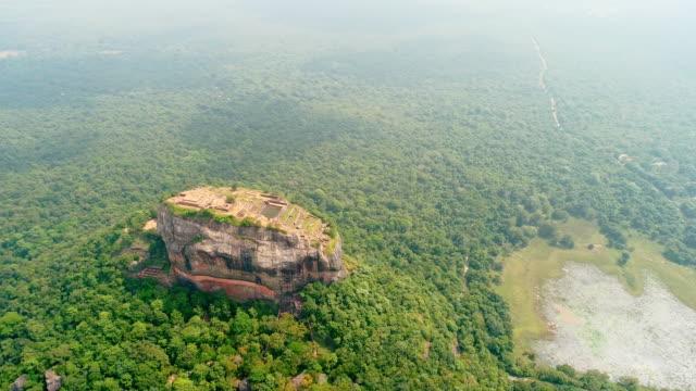 vidéos et rushes de ws escarpée rocheuse surplombant ensoleillé et verdoyant paysage verdoyant, sri lanka, sigiriya - inclinaison vers le bas