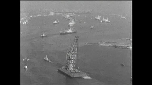 A crane barge cruises through Tokyo Bay during postwar land reclamation.