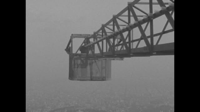 crane boom lowers with cameraman shooting footage of city as it comes into view his hand is visible cranking the camera as he faces the city / note... - crane stock videos & royalty-free footage