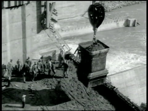 vidéos et rushes de crane bucket moving concrete down to men below dredging crane moving materials from water dumping on land high voltage metal towers africanamerican... - 1936