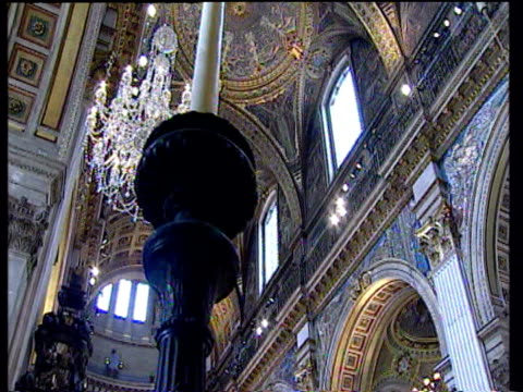 crane down on interior of st pauls cathedral with ornate ceiling arches and chandelier in background and large candle stick holder in foreground... - golden jubilee stock videos & royalty-free footage