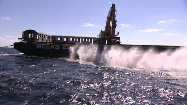 A crane drops rail cars off the side of a barge and into the sea.