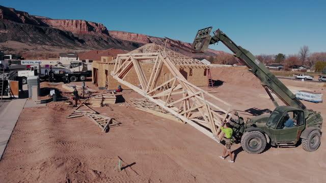 vídeos de stock, filmes e b-roll de um guindaste, operador de empilhadeira, levantando treliças recém-construídas, para serem colocadas no lugar pelos armadores de construção em uma nova casa que está sendo construída - levantar