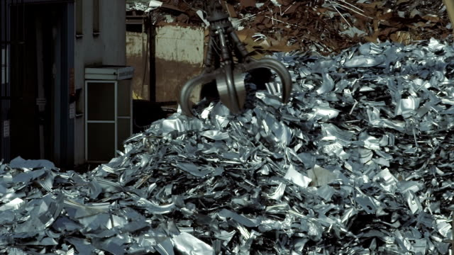 vidéos et rushes de crane paire en métal et les déversant sur pile - grue engin de chantier