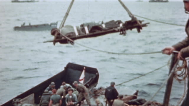 crane hoist lifting casualties on stretchers from tank deck of lst through open hatch above and lowering them to pontoon barge alongside during world... - battle of iwo jima stock videos and b-roll footage