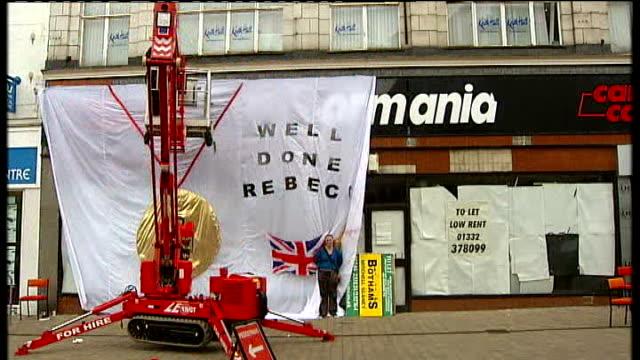 crane hoisting banner up over shop front - hoisting stock videos & royalty-free footage