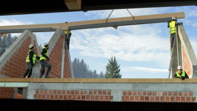 ld crane holding a wooden beam in the air so the builders can put it into place - elmetto protettivo da lavoro video stock e b–roll