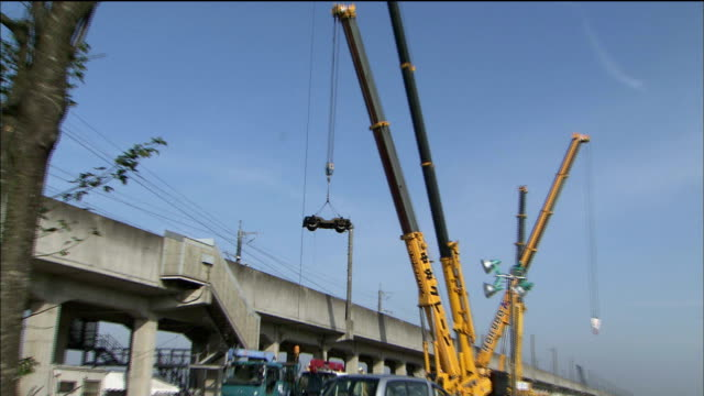 crane holds a set of railroad wheels over an elevated track after the chuetsu earthquake. - 脱線点の映像素材/bロール